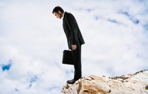 Man in business suit looking down from a cliff